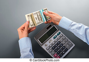 Woman counting money with calculator.