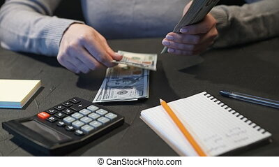 Woman counting US currency on home table with calculator. Female person counts dollars - money. New banknotes in hands. . High quality 4k footage