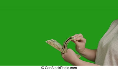 Woman counts a large stack of money, green screen