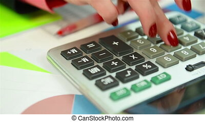 Hand Businesswoman Counts The Annual Report On Calculator