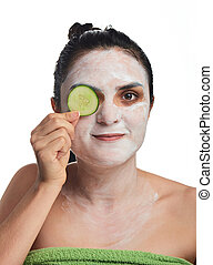 woman cover her eye with cucumber