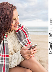 Woman covered in blanket with cellp