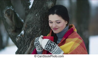 Woman covered with a cup of tea in winter park