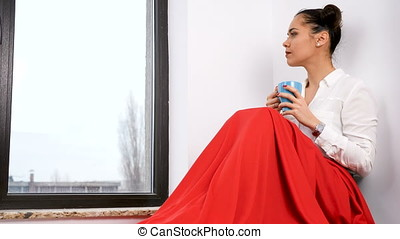 Woman covered with red blanket sitting next to a big window