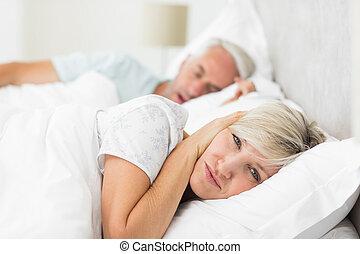 Woman covering ears while man snori - Closeup of a woman...
