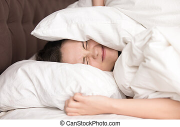 Woman covering head with pillow because of noise