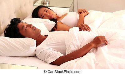 Woman covering her ears as partner is snoring loudly at home...