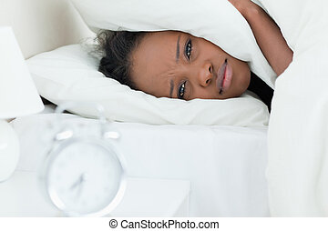 Woman covering her ears while her alarm clock is ringing