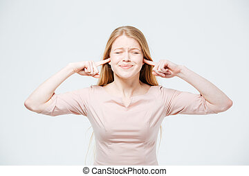 Woman covering her ears with fingers