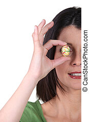 Woman covering her eye with easter egg