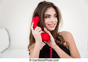 Woman covering microphone on the red phone tube