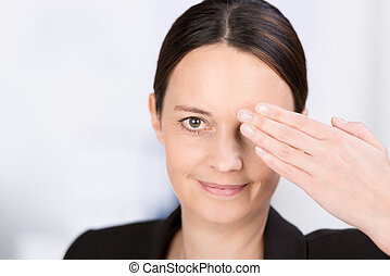 Woman covering one eye with her hand - Attractive serious...