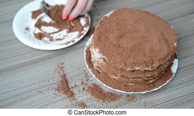 Woman covers cake with biscuit crumbs - Woman covers cake...