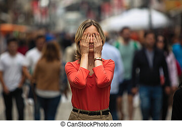 Woman covers his eyes during panic attack in public place.