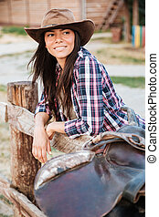 Woman cowgirl leaning on fence in village and looking away -...