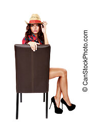 woman cowgirl sitting on a chair isolated on white