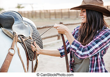 Woman cowgirl standing and putting saddle on horse -...