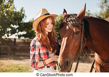Woman cowgirl taking care of her horse on ranch - Cute...
