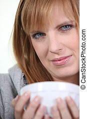 Woman cradling a breakfast bowl in her hands