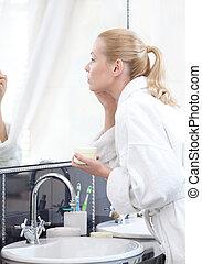 Woman creams her face in bathroom