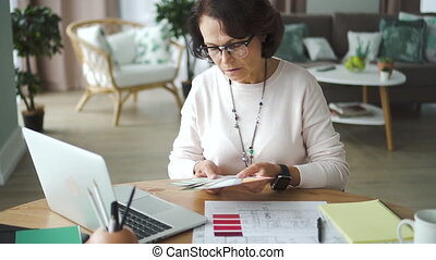 Woman creative designer working with project at table with laptop in home office.