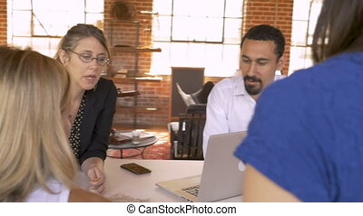 Woman creative team leader discussing ideas with entrepreneur coworkers