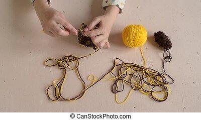 Woman crocheting yellow and brown yarn