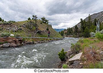 Woman Crosses Footbridge Over Rushing Water