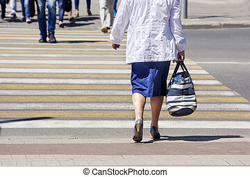 woman crossing a street in the city