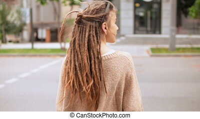 woman crossing the road - back view girl with dreadlocks...