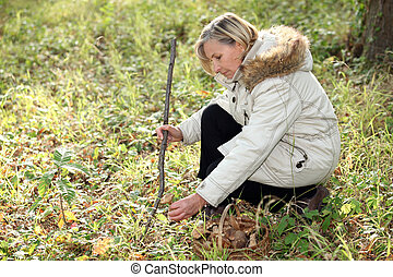 Woman crouching in woods looking at leaves