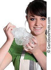 Woman crushing a plastic bottle