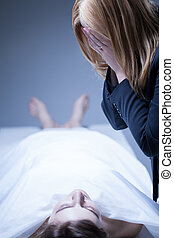 Woman crying in morgue