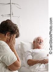 Woman crying next to her sick husband