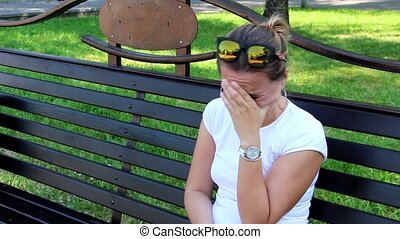 Woman crying sitting on a bench
