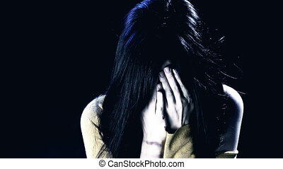 Woman crying with hand in face