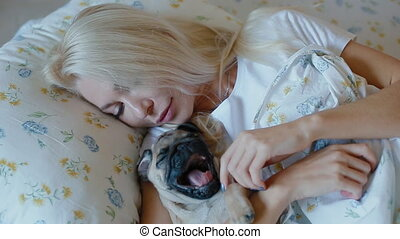 Woman cuddling kissing puppy pug