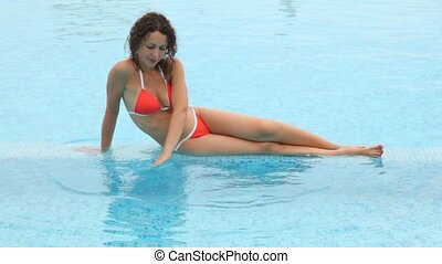 Woman cuit sits in pool shallow water