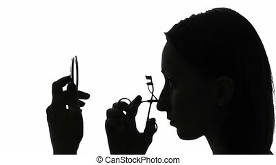 Woman curling her eyelashes - Silhouette of a woman curling...