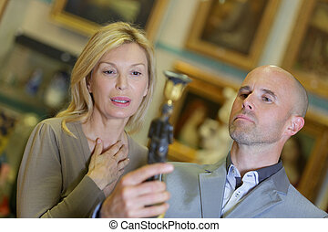 woman customer haggles with antiques seller