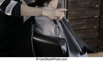 woman customer sits on an armchair in a beauty salon.