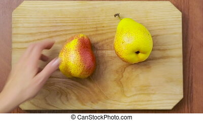 woman cuts a pear on a wooden board. top view