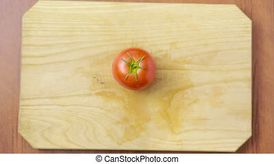 woman cuts a tomato on a wooden board. view from above. top view
