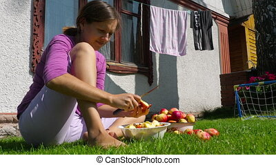 Woman cuts apples for jam outdoor at sunny autumn day