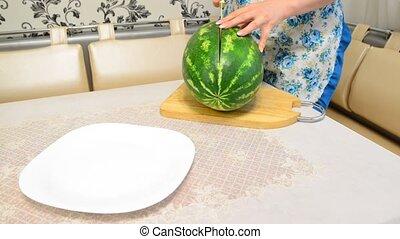 woman cuts  big ripe watermelon