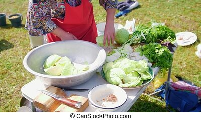 Woman cuts cabbage during a hike, on the table a lot of...