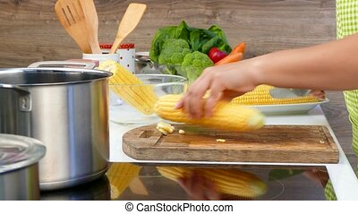 woman cuts corn in the kitchen - Female hands cut off excess...