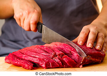 woman cuts fresh meat in the kitchen