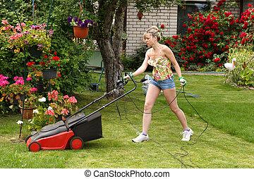 Woman cuts the grass