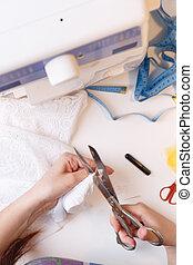 Woman cuts thread in fabric